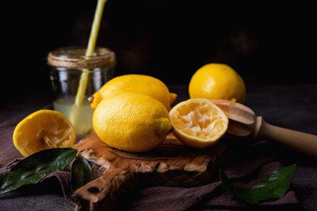 Ripe juicy organic lemons on a wooden board, dark background