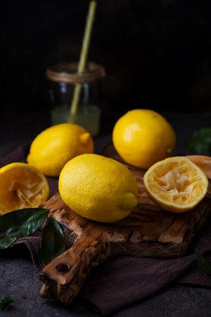 Ripe juicy organic lemons on a wooden board, dark background, close up 版權商用圖片