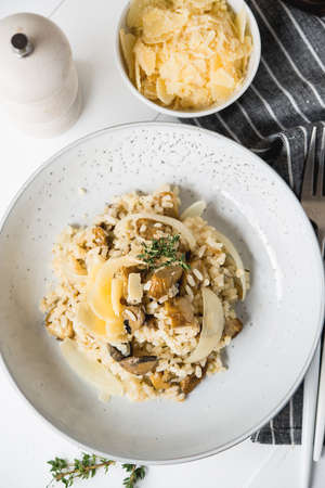 Risotto with porcini mushrooms and parmesan on a light background, top view