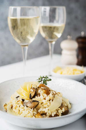 Risotto with porcini mushrooms and parmesan on a light background, selective focus, close up 版權商用圖片