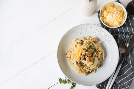 Risotto with porcini mushrooms and parmesan on a light background, top view, copy space