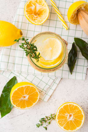 Homemade refreshing lemonade, detox drink with lemon and herbs on a light background, top view
