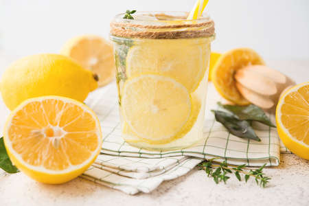 Homemade refreshing lemonade, detox drink with lemon and herbs on a light background, close-up