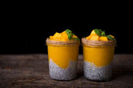 Homemade healthy breakfast, chia pudding with coconut milk and mango on a wooden table, copy space