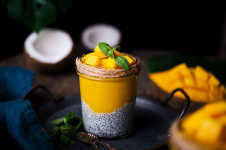 Homemade healthy breakfast, chia pudding with coconut milk and mango on a wooden table 版權商用圖片