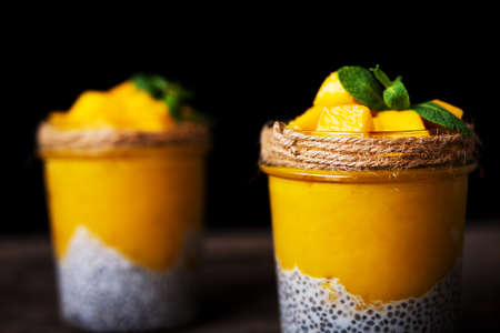 Homemade healthy breakfast, chia pudding with coconut milk and mango on a wooden table, selective focus