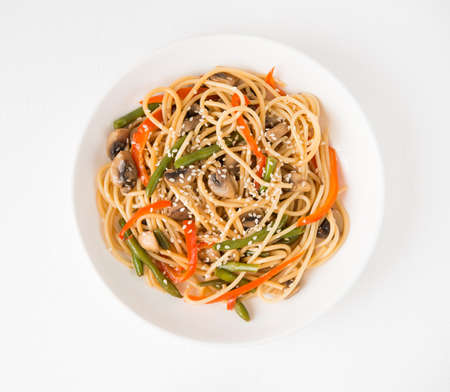 Noodles with vegetables (string beans, bell peppers, sesame seeds) and mushrooms in soy sauce, traditional Asian food, top view