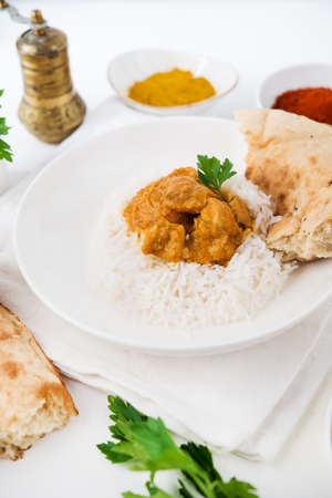 Chicken with rice in curry sauce-a traditional Indian dish on a white background, close up