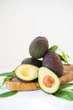 Mature ripe avocado haas with leaves on a white background, selective focus, copy space Zdjęcie Seryjne