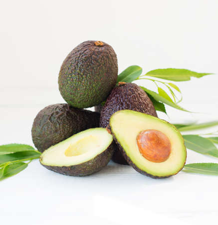 Mature ripe avocado haas with leaves on a white background, selective focus