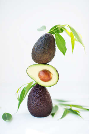 Haas avocado with leaves on a white background, selective focus, creative picture