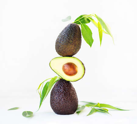 Haas avocado with leaves on a white background, selective focus, creative picture Zdjęcie Seryjne