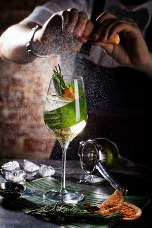 Bartender squeezing lemon juice into cocktail. Green elegant cocktail on the black table.
