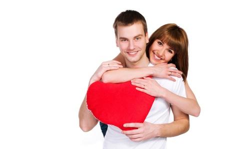 parejas enamoradas: Pareja con un coraz�n rojo sobre fondo blanco Foto de archivo