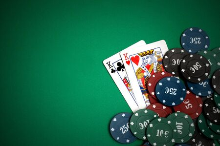 Cards and poker chips on a green background