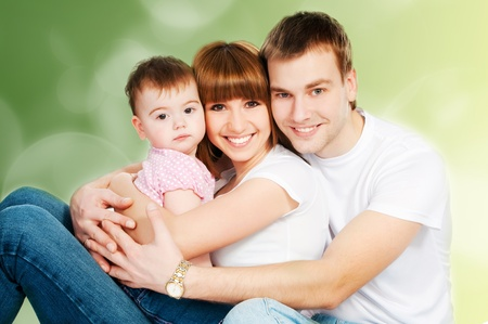 happy family with a baby on a color background photo