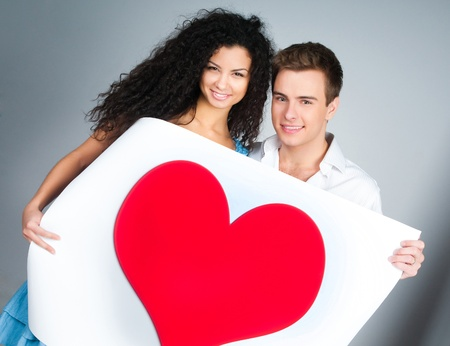 beautiful young couple holding a red heart Stock Photo - 8907344