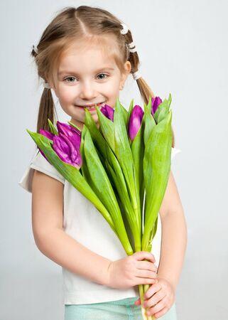 jolie petite fille: belle petite fille avec un bouquet de tulipes