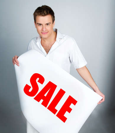 young man with a placard sale on a lihgt photo