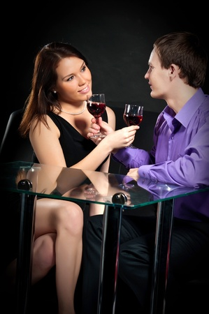 Loving couple toasting with wineglasses over a black background Stock Photo - 9101336