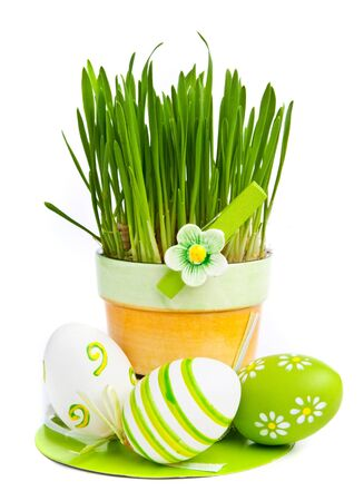 Hand painted Easter eggs and grass isolated on white background photo