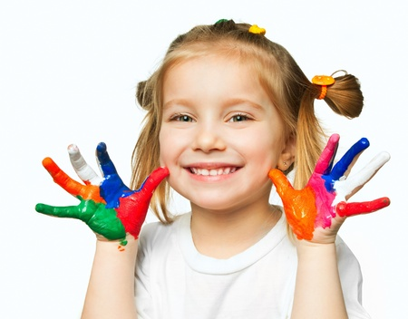 beautiful little girl with her ??hands in the paint Фото со стока