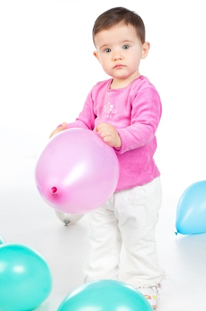 small child with colorful balloons in the studio photo