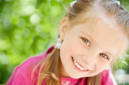 kid smiling: cute little girl smiling in a park close-up