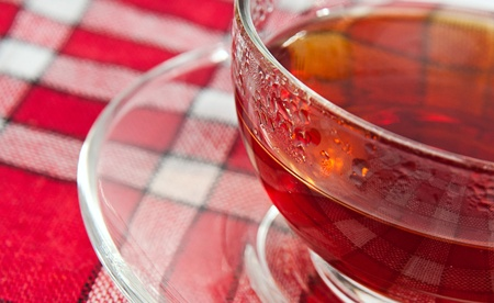 transparent cup of tea on red tablecloth photo