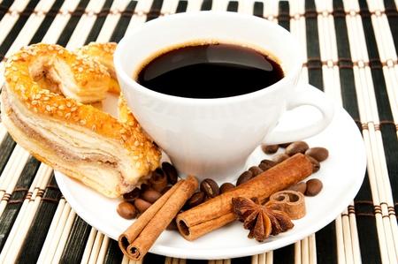 tarde de cafe: galletas, café y canela sobre un mantel con bandas Foto de archivo