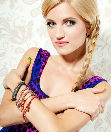 Beautiful blonde girl on a background wall with patterns photo