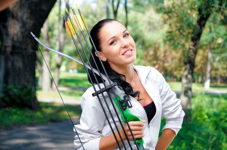 young woman with a bow and arrows in the woods photo