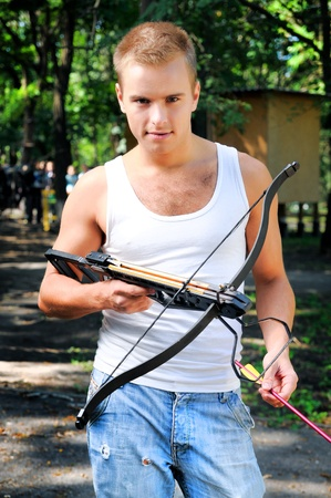 crossbow: A young man with a crossbow and arrows in the woods