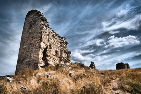 ruins is ancient: ruined castle stands in a field against sky