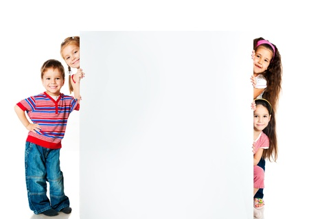 niños sosteniendo un cartel: los niños al lado de una pared blanca para texto o imagen