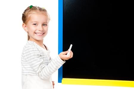cute little girl standing near blackboard isolated on white photo
