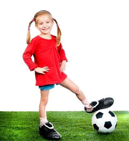 little girl with soccer ball in boots on a green lawn photo