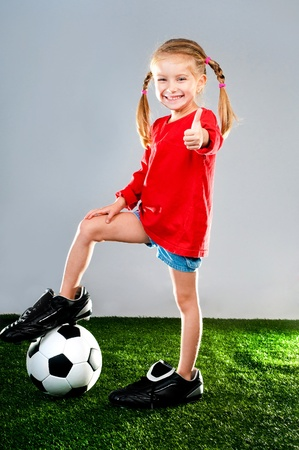 child ball: little girl with soccer ball in boots on a green lawn Stock Photo