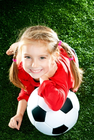 female soccer: little girl with soccer ball in boots on a green lawn Stock Photo