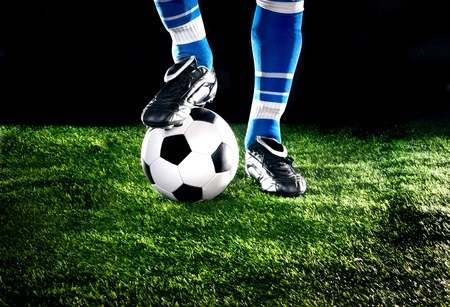 soccer ball on grass: soccer ball with his feet on the football field Stock Photo