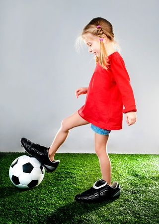 fitness goal: girl with soccer ball in boots on a green lawn