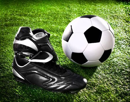 soccer ball and shoes on a green lawn photo
