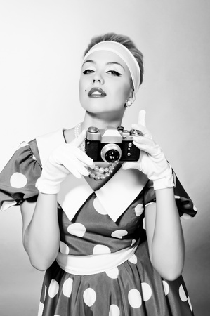 beautiful young lady with a camera in retro style photo