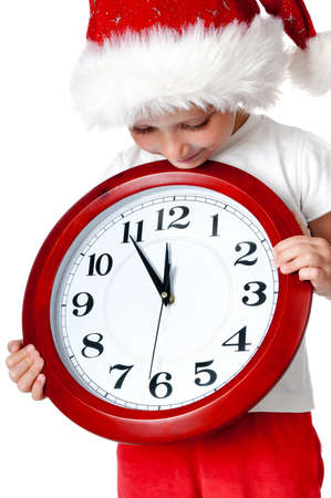 cute little girl in santa cap with a clock isolated oin white photo
