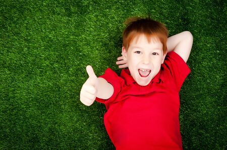 cute little boy lying on a green lawn photo