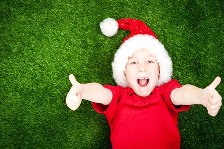 cute boy in santa hat on the green grass with thumbs up photo