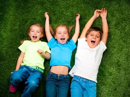 lying on grass: small kids lie on the green grass