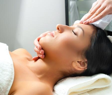 massaggio collo: Giovane e bella donna riceve massaggio del viso con gli occhi chiusi in un centro termale Archivio Fotografico
