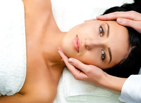 Piękna młoda kobieta otrzymania masaż twarzy patrząc na kamery w centrum spa