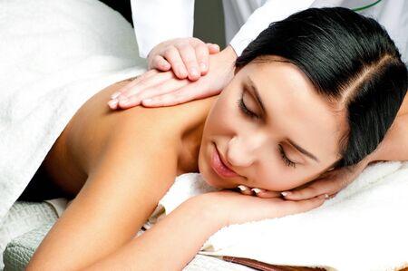 detras de: bella mujer recibiendo un masaje de espalda con los ojos cerrados en un centro de spa